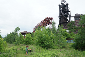 visitors read an Iron Garden cast                                   sign while walking an edited path to                                   the furnaces